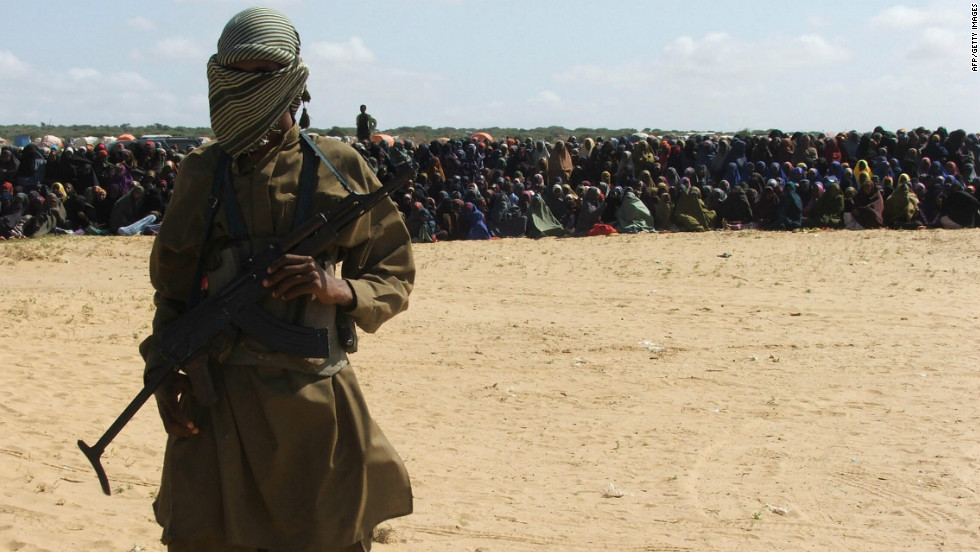 An Islamist fighter stands guard as hundreds of residents watch an amputation punishment carried out. Al-Shabaab's implementation of strict Sharia law has begun to alienate many in the way that al Qaeda did in Iraq. Women have been stoned to death for adultery; amputations and beheadings are common. In some areas Al-Shabaab has banned listening to the radio and non-Arabic signs; and it has assassinated several journalists.