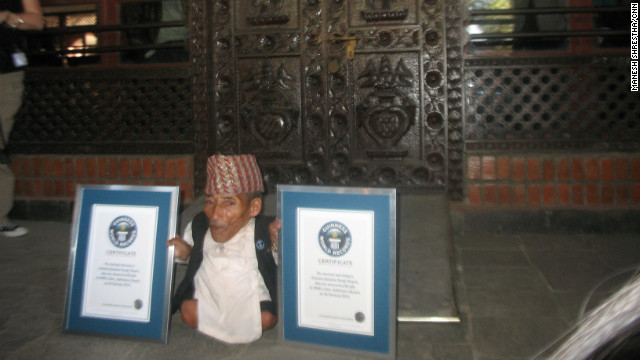 Chandra Bahadur Dangi displays two Guinness World Records certificates: for shortest man ever and shortest man living.