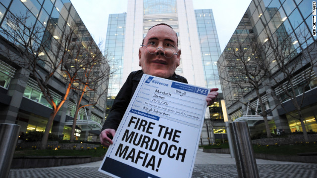A protester dons a mask of James Murdoch outside of News International office in London on Wednesday.