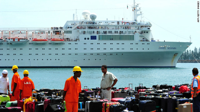 The Costa Allegra is towed into the harbor of Victoria in the Seychelles on March 1 as luggage waits on the quayside.