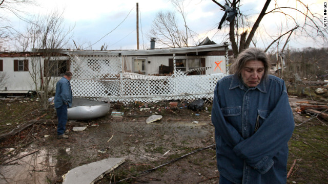 Steve Smith and J. J. Smith survey the damage to their home after Friday's tornado in Henryville, Indiana.