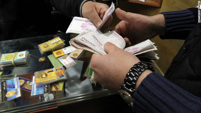 An Iranian trader exchanges a gold coin for cash in Tehran as sanctions make currency plummet in value.