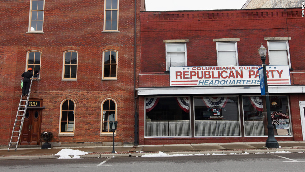 A worker cleans windows next to the Columbiana County Republican Party headquarters during Super Tuesday voting in Lisbon, Ohio.