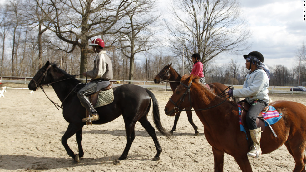 Leshaun Walker, Sihgerra Myers and Sydney Rutledge exercise horses in a paddock at the Chamounix Equestrian Center in Philadelphia's Fairmount Park, home to the Work To Ride long-term prevention program for middle- to high-school-aged youth.