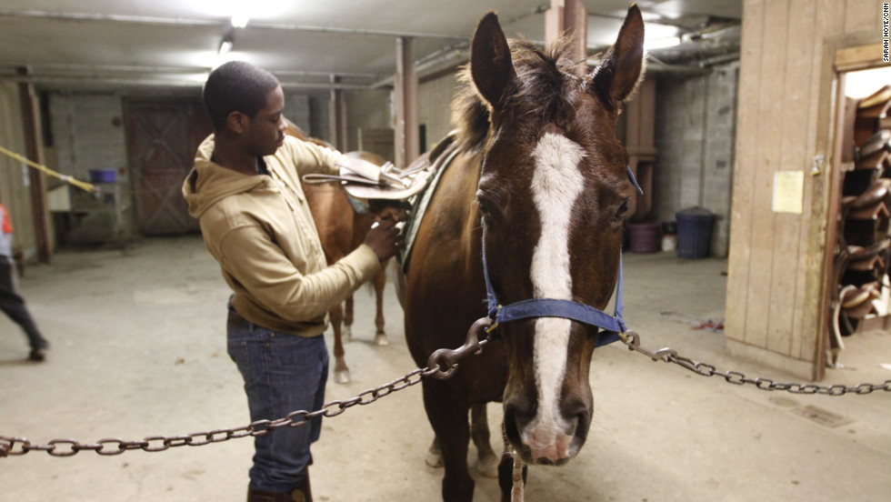 "Brandon Rease, 16, checks the saddle on his horse Billy. Rease said he never imagined he'd be riding horses or playing polo -- a sport usually reserved for royalty and the super rich. ""I guess in other people's eyes it's weird. But to us it's just normal habit that we do every day -- ride, play polo and travel,"" he said."