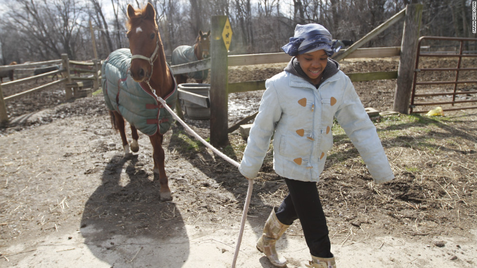 "Sydney Rutledge walks a horse barn to the stables before going out to ride. Rutledge, 15, once afraid of horses, now plays on the Work To Ride women's polo team. Last year, while Hiner was dropping her off at home, she heard gunshots. ""The worst thing I ever saw was (that) man get shot in front of me,"" she said.  ""That's why I don't like being around where I live."""
