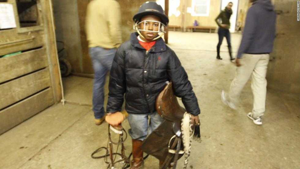 Brian Ferrell makes his way through the stable wearing his polo helmet and towing his horse's saddle. Ferrell, 13, joined Work To Ride five years ago. Ferrell, alongside his fellow riders, gets to ride horses in exchange for cleaning out stalls and brushing down horses.