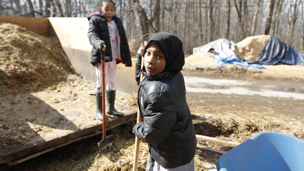 "Sudayaah Myers, 9, finishes her Saturday chores, including cleaning out horse stalls and dumping manure, alongside fellow rider, Aniyah Foreman, 9. ""I like coming here, we have a lot of fun,"" she said."