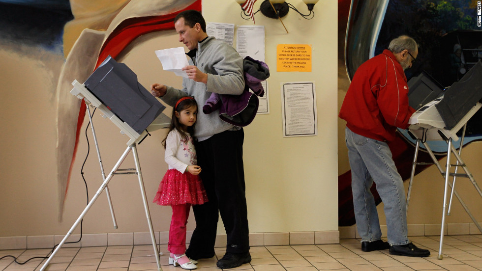 Sophia Walsh, 5, stands with her father, William Walsh, as he fills out his ballot Tuesday at a polling station set up in Froehlich's Classic Corner restaurant in Steubenville, Ohio.