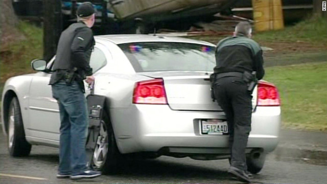 Officers take cover outside the courthouse after the stabbing and shooting incident in Montesano, Washington.