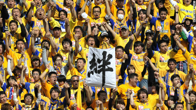 "Vegalta Sendai's fans hold up a banner reading ""Bond"" to show the close support they have for their team"