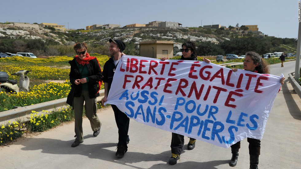 "Demonstrators against Le Pen's visit hold a banner reading ""Liberty, equality, fraternity, also for the illegal immigrants"" in French."
