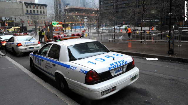 NYPD officers watch as workers clean Zuccotti Park on Sunday after Occupy Wall Street demonstrators were cleared from the park on Saturday.