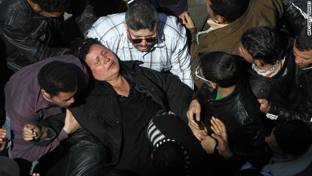 A woman faints as crowds converge on Saint Mark's Coptic Cathedral in Cairo's al-Abbassiya district, March 18, 2012.