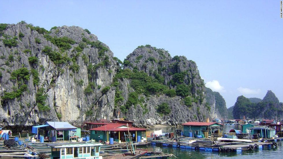 Large networks of floating villages hide in the shadows of the karsts in Halong Bay. Brightly colored huts are built on grids of floating barrels and beams.