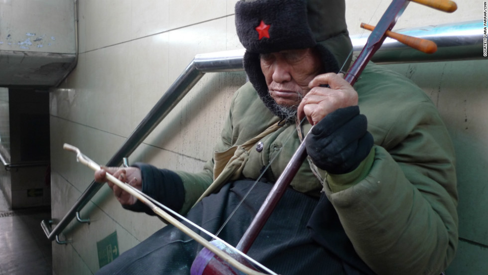 A blind man plays the erhu, a traditional Chinese instrument, in the entrance of a Beijing subway station.