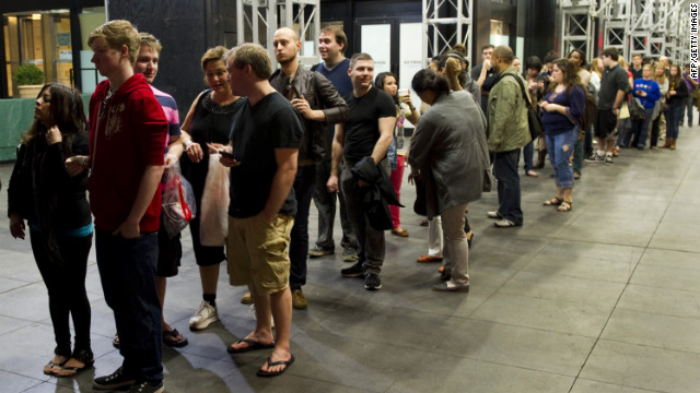 "Moviegoers wait in line for the opening of ""The Hunger Games,"" March 22 at the Ziegfeld Theatre in New York."