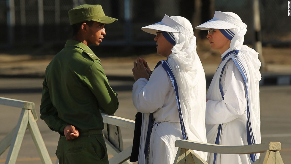 Sisters with Mother Teresa's Missionaries of Charity speak to a member of the Cuban military at Antonio Maceo Revolution Square.