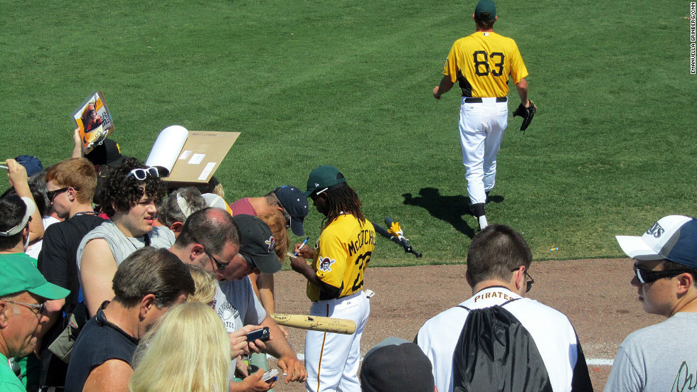 Pirates outfielder Andrew McCutchen signs memorabilia for fans before a spring training game at McKechnie Field.