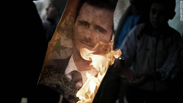 A Free Syrian Army member burns a portrait of President Bashar al-Assad, southwest of Homs, on January 25.