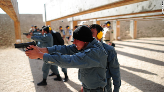Afghan police trainees practice using their guns as a German policeman watches near Camp Marmal in Afghanistan.