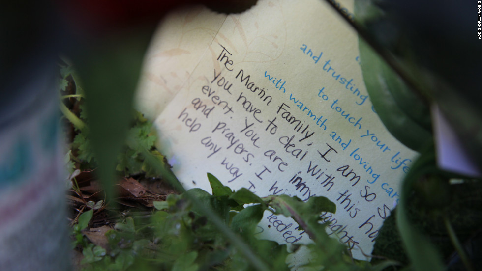 A handwritten card lies among the memorial gifts outside the neighborhood where the high schooler died.