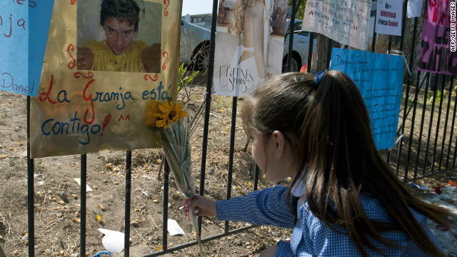 A girl places a flower in support of Chilean Daniel Zamudio outside the public hospital in Santiago on March 28, 2012.