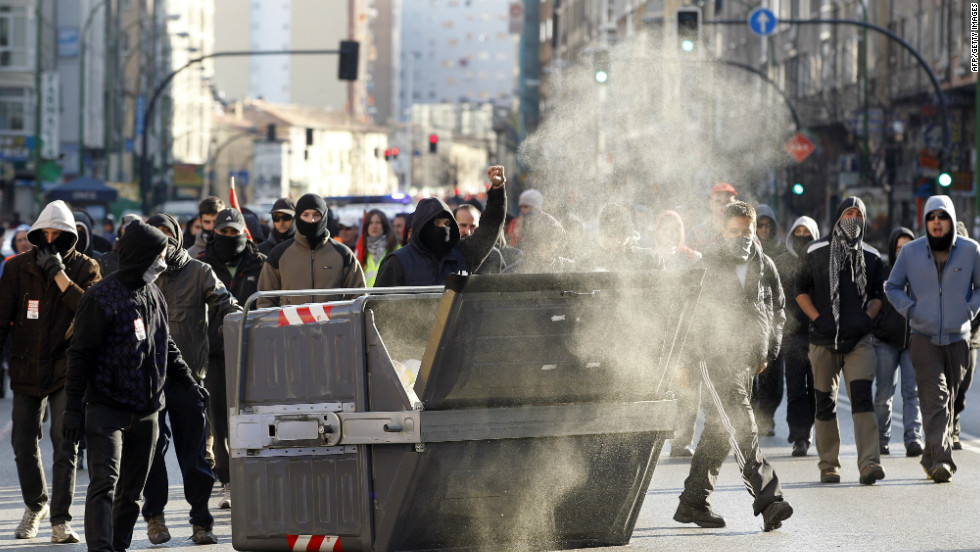 Protesters walks past a waste container in Burgos during a national strike on March 29.
