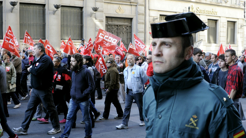 "A ""Guardia Civil"" police officer walks along desmonstrators during a day of national strike in central Madrid."