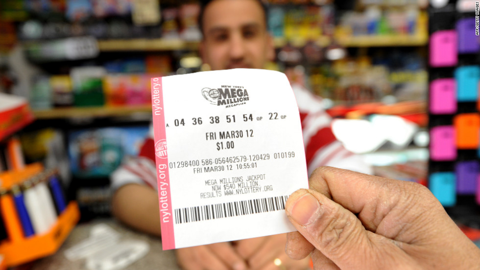 A man shows his Mega Millions ticket in front of clerk Abdulwali Mohamed Osaim at a convenience store on Manhattan's East Side.