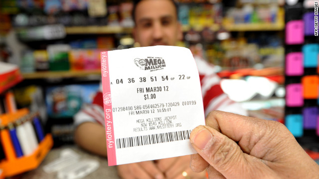 A man shows his Mega Millions lottery ticket in front of clerk Abdulwali Mohamed Osaim at a convenience store on the east side of Manhattan.