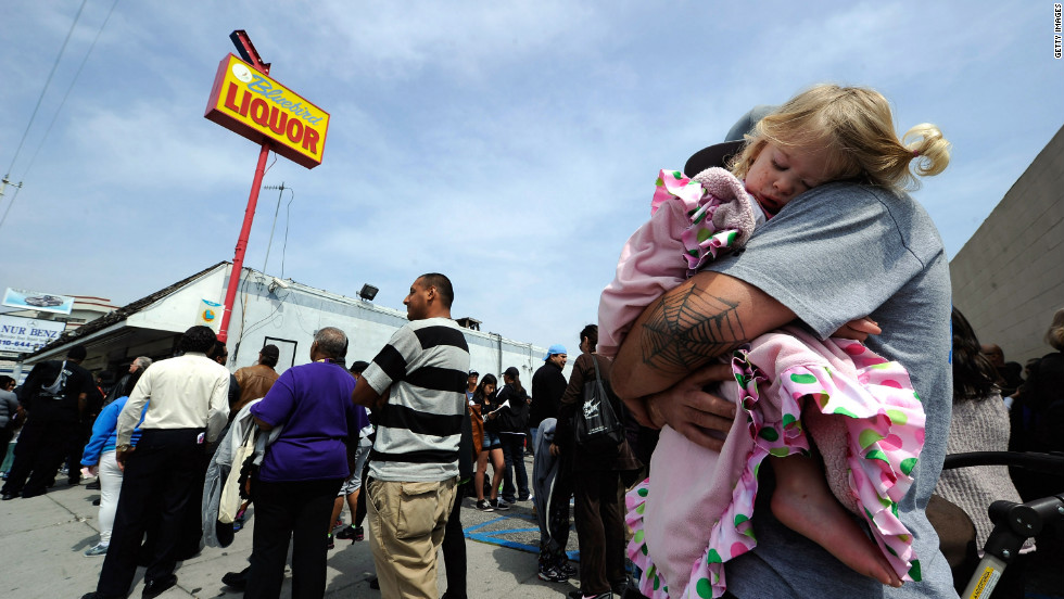 One year-old Karissa Sanchez sleeps on her father Chris' shoulder as they have been waiting over three hours to buy their Mega Millions lottery tickets at Bluebird liquor store.