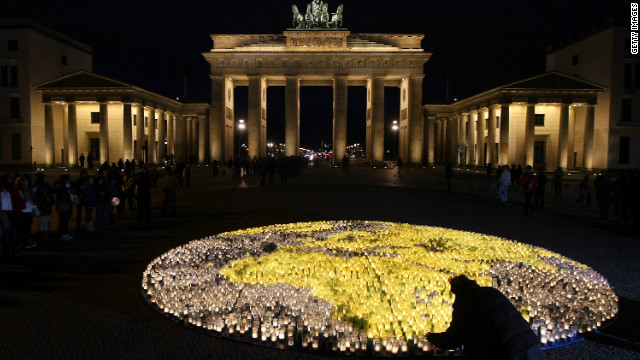 A volunteer lights one of 5000 blue and green candles in shape of Planet Earth in front of the Brandenburg Gate during Earth Hour 2012 on March 31 in Berlin.