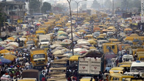 People walk struggling for space between buses and trucks at the popular Oshodi bus stop in Lagos.