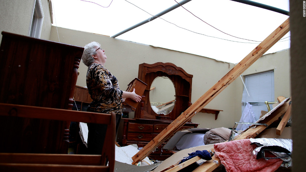 Patricia Daugherty searches through her belongings after her home was destroyed.