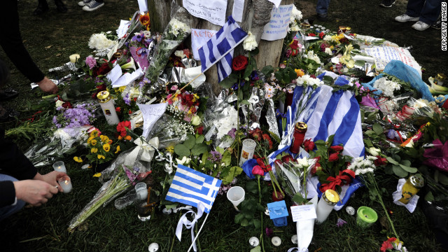 Greek flags along with flowers, candles and hand written messages lay on April 5, 2012 at the foot of a cypress tree where a retired pharmacist, had shot himself at Athens central Syntagma square. The 77-year-old, killed himself yesterday morning in the busiest public square of the Greek capital, opposite to the Greek Parliament, which for two years has been the main rallying point for demonstrations against government austerity measures. Greek newspapers on Thursday printed excerpts from a note, allegedly found in the pensioner's pocket, in which he accused the government of leaving him in penury and compared the administration to the regime imposed by Greece's Nazi German occupiers in 1941. AFP PHOTO / LOUISA GOULIAMAKI (Photo credit should read LOUISA GOULIAMAKI/AFP/Getty Images)