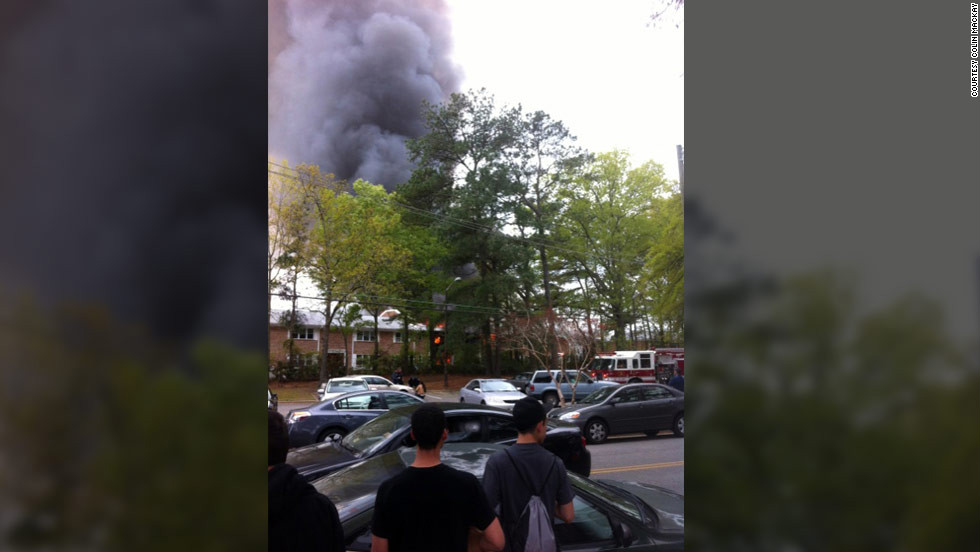 Spectators watch as smoke billows from an apartment building in Virginia Beach.