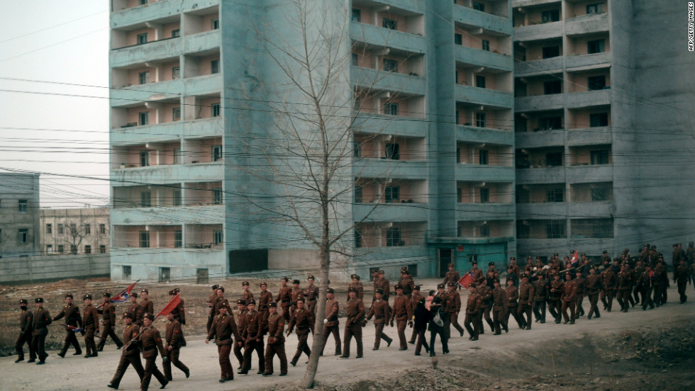 A troupe of North Korean soldiers is seen marching along the railway, carrying flags.