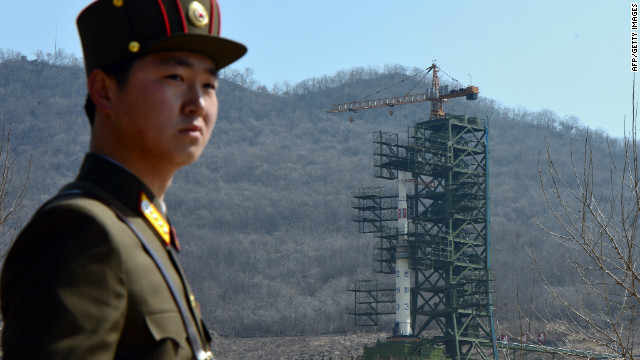 A North Korean soldier stands guard Sunday in front of the Unha-3 rocket in Tongchang-ri.
