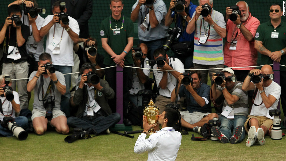 Djokovic plays up to the cameras after winning his first Wimbledon in 2011, beating Nadal 6-4 6-1 1-6 6-3 in a final lasting two hours, 28 minutes.