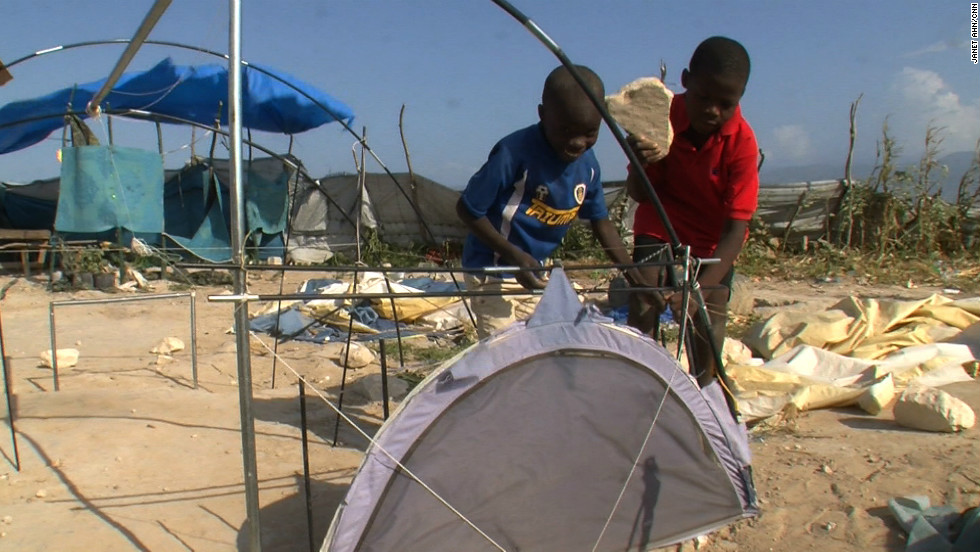 Two boys at the tent city orphanage work to fix their tent blown away by strong winds.