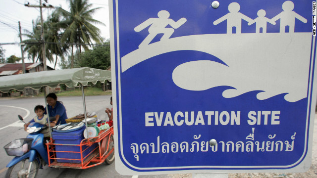 Thai family rides a motorcycle past a tsunami evacuation sign in Phang Nga province, 01 December 2006.