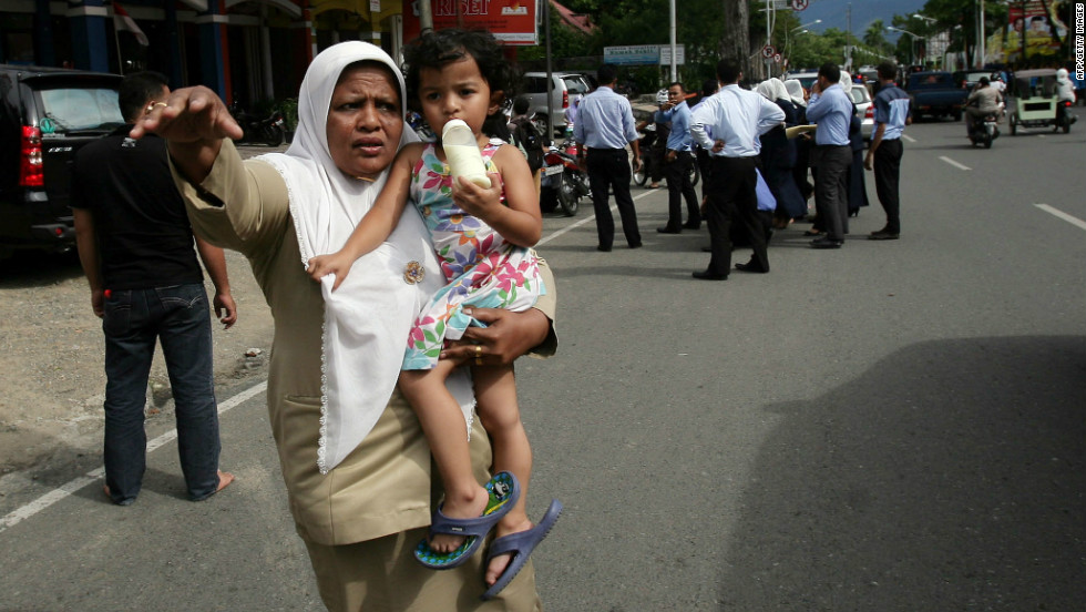 An Acehnese woman with a child tries to stop a car to go to higher ground shortly after Wednesday's earthquake.