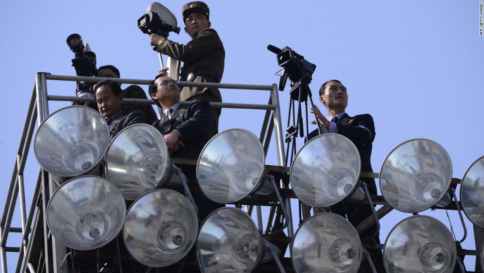 Members of the North Korean media look out from a viewing point during the parade.
