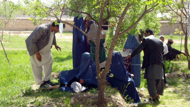 Sickened women receive treatment Tuesday in a courtyard in northeast Afghanistan; IV bags are hung from tree branches.