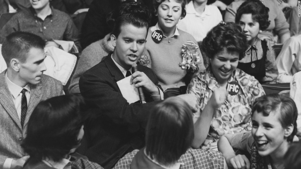 """American Bandstand"" host Clark, pictured in 1958, surrounded by audience members."