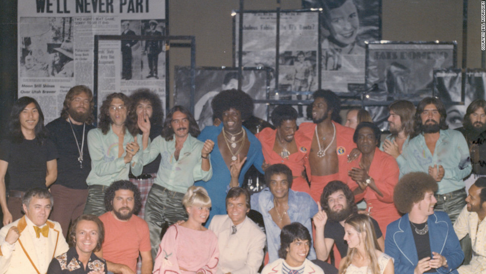 "Drummer Bill Rodriguez was among those who posed for this large group photo with Clark for his Las Vegas show in the 1970s. Rodriguez admitted to a mistake in one of the performances: ""I was so nervous I launched into the 'Bandstand' theme all by myself before Dick's monologue, leaving Dick alone on the stage with a mic while I played by myself before realizing I'd just massively blown it. Dick just told the audience, 'Ah, the enthusiasm of youth,' and made it seem as if it was part of the show. """