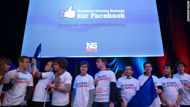 Young supporters wait for Nicolas Sarkozy, as a giant screen provides his Facebook adress during a campaign meeting in Lille.