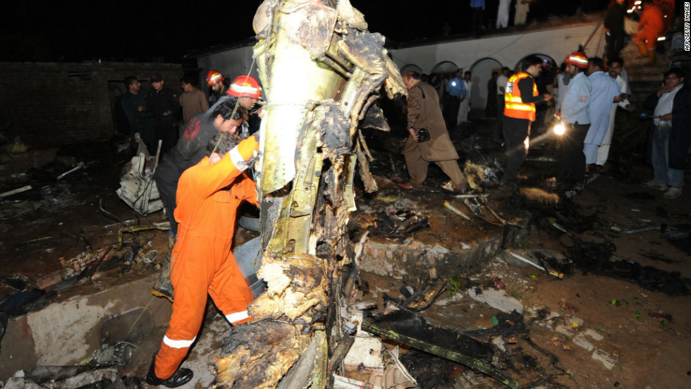 Rescue workers and local residents search the site of a plane crash in Rawalpindi, Pakistan, on Friday.