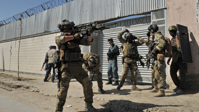 A member of the foreign forces points gun at building being used by insurgents near scene of an attack in Kabul last week